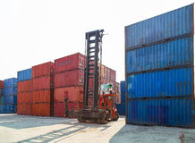 Forklift handling container box loading to truck in import export logistic zone. royalty free stock photography