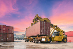 Forklift handling the container box packed up transport trucks. Stock Photo