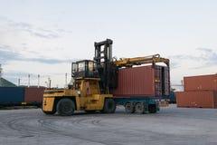 Forklift jest ładowniczym zbiornika pudełkiem przewozić samochodem przy dworcem blisko Fotografia Royalty Free