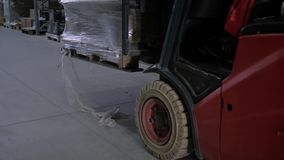 Forklift kierowca podnosi w górę pudełek z merchandise w ampuła magazynie