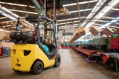 The forklift is in a large and light warehouse. Yellow color stock images