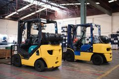 The forklift is in a large and light warehouse. Yellow color. royalty free stock photography