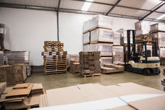 Forklift in a large warehouse. Forklift amid rows of boxes in a large warehouse Royalty Free Stock Image