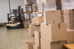 Forklift in a large warehouse. Forklift amid rows of boxes in a large warehouse Royalty Free Stock Photos