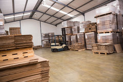 Forklift in a large warehouse. Forklift amid rows of boxes in a large warehouse Stock Photo
