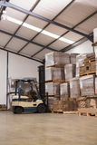 Forklift in a large warehouse. Forklift amid rows of boxes in a large warehouse Royalty Free Stock Images