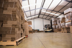Forklift in a large warehouse. Forklift amid rows of boxes in a large warehouse Stock Photography