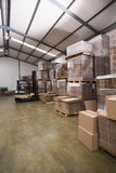 Forklift in a large warehouse. Forklift amid rows of boxes in a large warehouse Stock Photos