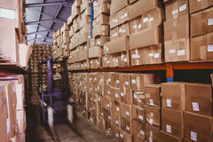 Forklift in large warehouse. Forklift amid rows of shelves with boxes in large warehouse Royalty Free Stock Photography