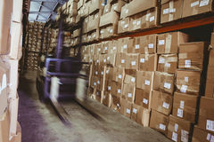 Forklift in large warehouse. Forklift amid rows of shelves with boxes in large warehouse Royalty Free Stock Images