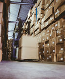Forklift in large warehouse. Forklift amid rows of shelves with boxes in large warehouse Stock Photos
