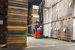 Forklift lifting a pallet. Reach truck forklift lifting a pallet from the top shelf in a large warehouse Stock Photography