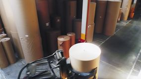 Forklift loader carries paper roll along pass in storehouse. Red forklift loader carries huge paper roll along pass between cardboard stacks in spacious stock footage