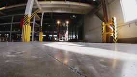 Forklift loader drives along plant warehouse low angle shot. Powerful forklift loader drives along production plant warehouse with stone floor approaching camera stock video footage