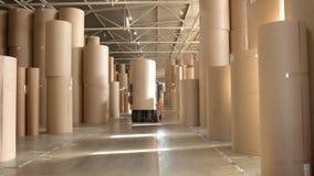 Forklift loader transports huge roll of paper in warehouse