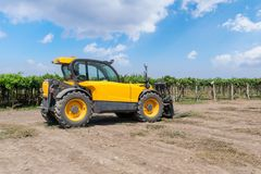 Forklift loader of yellow color in a field on a vineyard background. royalty free stock photo