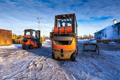 Forklift loaders for warehouse are waiting work outdoors during frosty day in the cargo center. Pallet stacker trucks in stock images