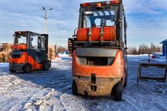 Forklift loaders for warehouse are waiting work outdoors during frosty day in the cargo center. Pallet stacker trucks in stock photos