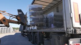 Forklift loads the truck with pallets of finished concrete products.  stock video