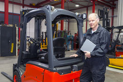 Forklift mechanic with manual Stock Photo