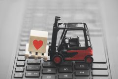 Forklift with red heart symbol on wooden block over laptop keyboard stock photos