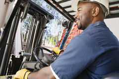 Forklift Operator. Happy African American industrial worker driving forklift at workplace stock photo