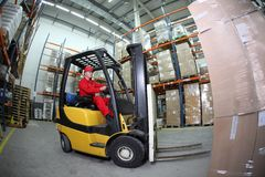 Forklift operator at work in warehouse Stock Images