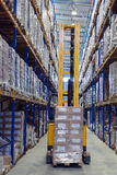 Forklift pallet truck traveling along the narrow aisle goods war Stock Photo