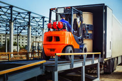 Forklift is putting cargo from warehouse to truck Stock Photo