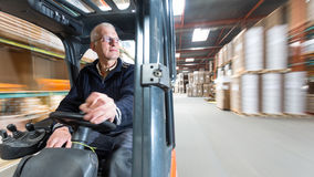 Forklift ride. Elderly man driving a forklift trough a warehous where cardboard boxes are stored royalty free stock photos