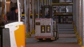 Forklift rides between rows in a warehouse, a man drives a forklift in a warehouse.