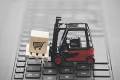 Forklift with shopping cart graphic on wooden block over laptop keyboard royalty free stock photos
