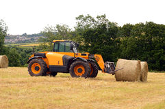Forklift / telehandler with straw bales in field. Yellow telehandler taking a break from loading bales in a farmers field Royalty Free Stock Photos