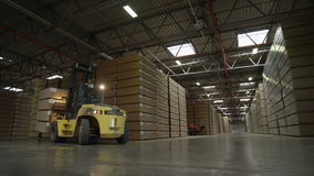 Forklift Truck with Cargo Drives between High Parquet Rows. KAZAN, TATARSTAN/RUSSIA - AUGUST 06 2015: Modern yellow forklift truck with cargo drives between high stock footage