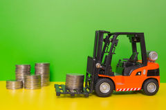 Forklift truck delivering coins. A powered industrial truck used to lift and move materials short distances royalty free stock photos