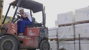 Forklift truck driver in a factory or warehouse driving between rows of shelving with stacks of boxes and packaging. Materials stock video