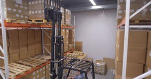 Forklift truck lift cargo in warehouse. Moving down shot stock video