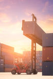 Forklift truck lifting cargo container in shipping yard Royalty Free Stock Photography