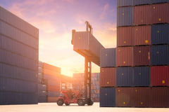 Forklift truck lifting cargo container in shipping yard or dock. Yard against sunrise sky with cargo container stack in background for transportation import Royalty Free Stock Images