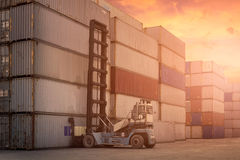 Forklift truck lifting cargo container in shipping yard Stock Photos