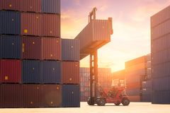Forklift truck lifting cargo container in shipping yard or dock yard. Against sunrise sky with cargo container stack in background for transportation import royalty free stock photo