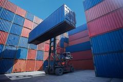 Forklift truck lifting cargo container in shipping yard or dock yard against sunrise sky for transportation import. Export and logistic industrial stock photos