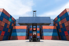 Forklift truck lifting cargo container in shipping yard Stock Images