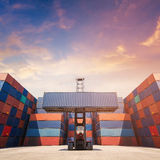 Forklift truck lifting cargo container in shipping yard Stock Image