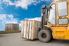 Forklift truck transporting wood cargo box. Forklift truck stacker transporting cargo to factory warehouse Stock Image