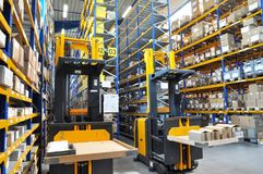 Forklift truck in a warehouse of a commercial enterprise, high r. Acks with products for assembly and shipping royalty free stock photos