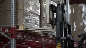 Forklift Trucks load Pallets with Cardboard Boxes at modern warehouse. Forklift Trucks Move Between Large Metal Shelves at a Modern Warehouse and Unload Pallets stock video