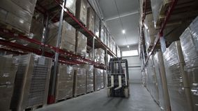 Forklift Trucks Move Between Large Metal Shelves at a Modern Warehouse. And Unload Pallets with Cardboard Boxes stock footage