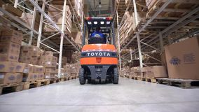 Forklift Trucks Move Between Large Metal Shelves at a Modern Warehouse and Unload Pallets with Cardboard Boxes Royalty Free Stock Photography