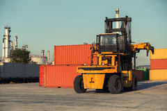 Forklift unloading and container stack in yard cargo shipping., Heavy equipment. Royalty Free Stock Photos